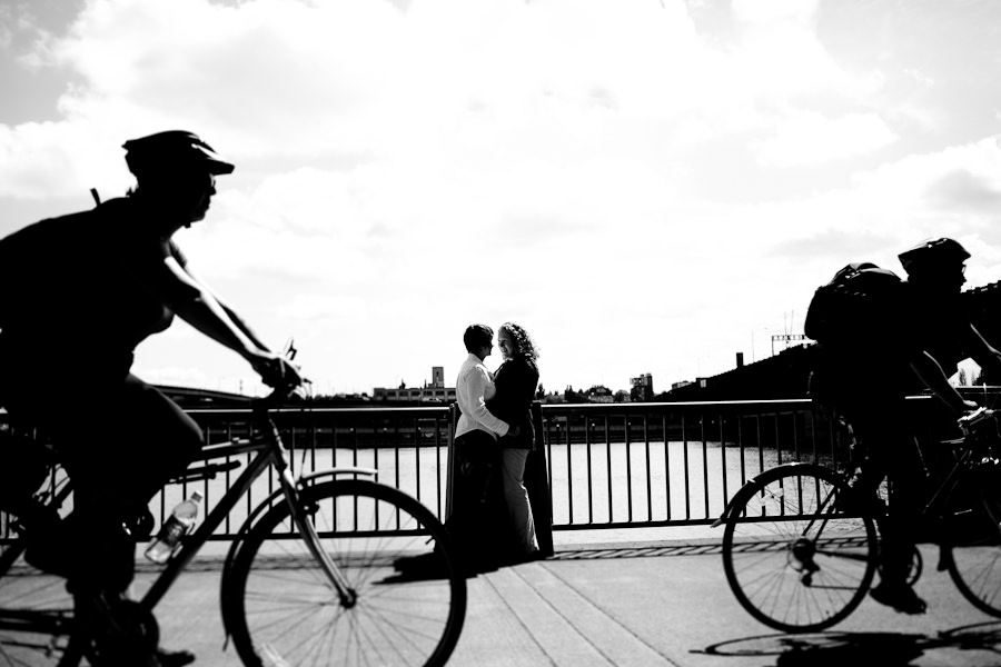 Creative photo of a couple framed in between two bikes on Portland's waterfront captured by Daniel Stark