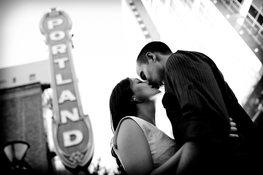 A cute couple pose under the Portland sign downtown for a photo taken by wedding photographer Daniel Stark of Portland, Oregon.