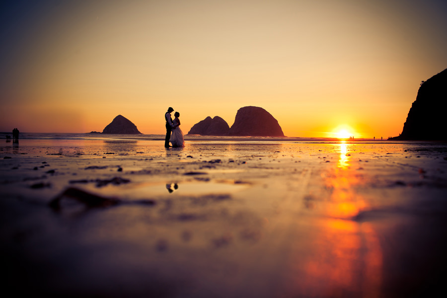 A couple kiss at sunset on the beach of Oceanside, Oregon after their beach wedding.