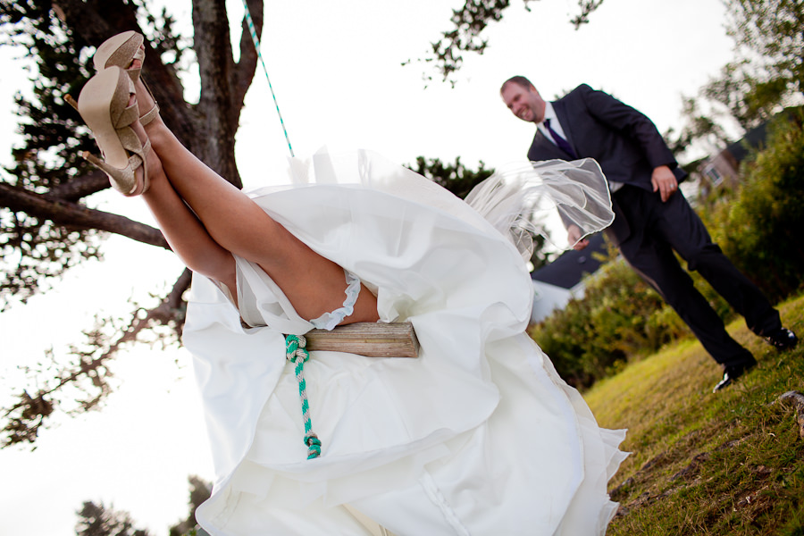 A fun shot of a bride on a rope swing being pushed by the groom photographed by Daniel Stark Photography.