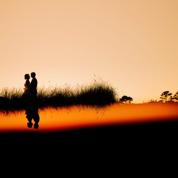A beautiful outdoor wedding on the Oregon Coast with a sunset over the Pacific Ocean with the wedding couple.